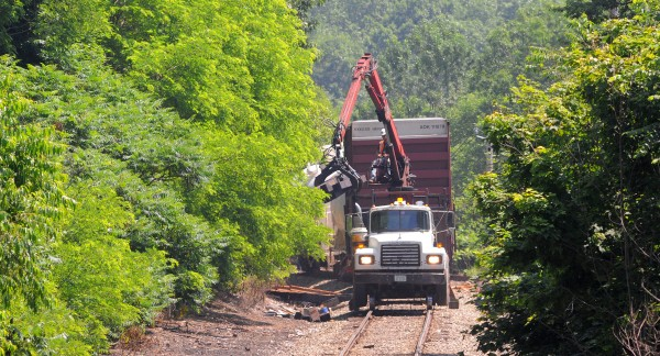 A truck unloads railroad ties at near a freight train that derailed on the Bangor-Veazie town line.