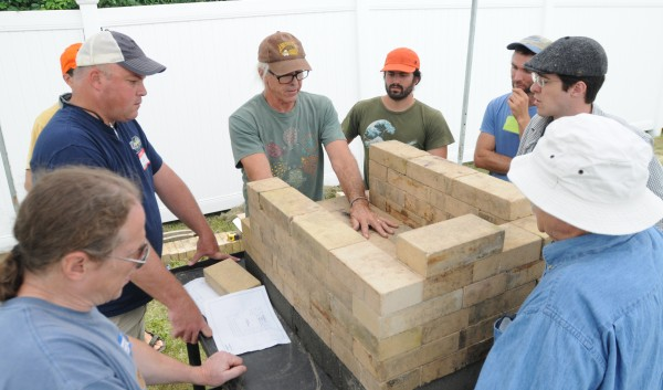 J. Patrick Manley III instructs a small group of wood-fired oven hobbyist on how to build a brick oven during the Kneading Conference held at the Skowhegan Fairgrounds on Thursday.