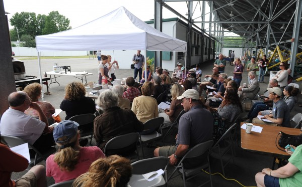 A small crowd of about 50 people gather around Dawn Woodward and Naomi Duguid as they put on a yeasted crackers workshop during the Kneading Conference held at the Skowhegan Fairgrounds on Thursday.