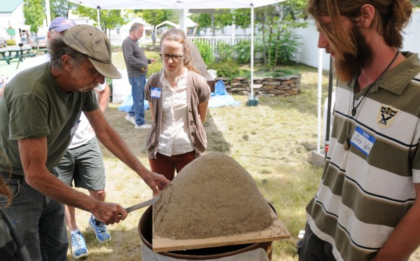 Alex West, right, of Hartland watches as Stu Silverstein, left, leads a workshop on earth oven building during the Kneading Conference held at the Skowhegan Fairgrounds on Thursday.