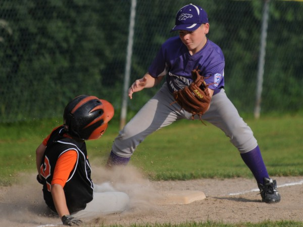 Bronco Little League third baseman Wyatt Harriman watches Brewer's CJ Horr slide safely back into third base after being caught in a rundown between bases during the third inning of the District 3 Little League championship for ages 11-12 in Brewer on Tuesday.
