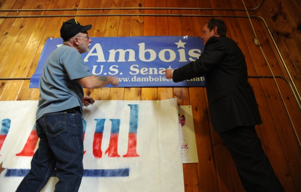 Skip Colson, left, Town of Alexander coordinator for Scott D'Amboise, and Mark Willis, right, Washington County coordinator for D'Amboise hang a banner in support of their candidate at the Washington Academy gym during the Washington County Republican Super Caucus on Saturday, Feb. 18, 2012.