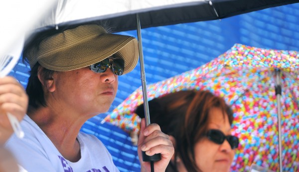 Sharyn Sonan of Pearl City, Hawaii (left) and Debbie Kushima of Waipahu, Hawaii take shelter from the sun under their umbrellas during the Canada versus Hawaii game during the 2013 Senior League World Series in Bangor Monday.  Sonan's grandson and Kushima's son both play on the Hawaii team.