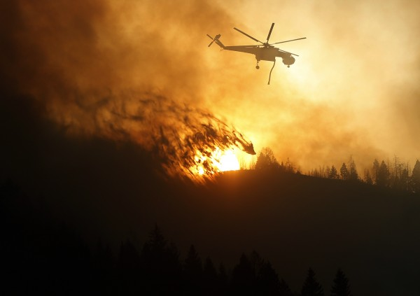 A helicopter air tanker dumps water as the sun sets at the Beaver Creek wildfire outside Hailey, Idaho August 17, 2013. A fast-moving central Idaho wildfire forced the evacuation of 2,250 homes near the tourist towns of Hailey and Ketchum as firefighters lost ground on Saturday against the blaze that also threatens the Sun Valley ski resort.