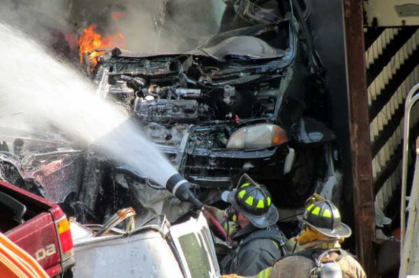 Firefighters spray flame-suppressing foam on blazing junked vehicles at West Paris Metals on Maple Street on Monday afternoon.