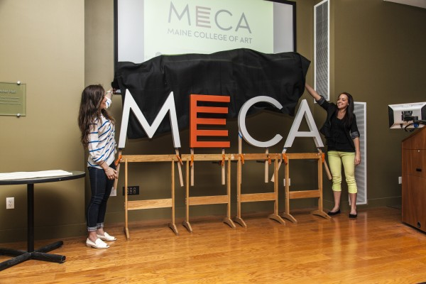 Maine College of Art students Sarah Mohammadi (left) and Hannah Sherwood pull the sheet off a school's new logo, created during a three-day intensive workshop by a team of MECA students, faculty and consultants. The unveiling took place during a May news conference at the Portland school.