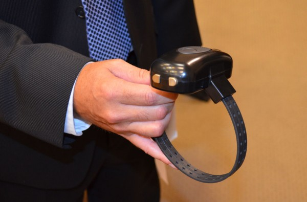 Maine Rep. Kenneth Fredette, R-Newport, (second from left) holds an electronic monitoring device that is capable of alerting domestic violence victims that their abuser may be headed their way.