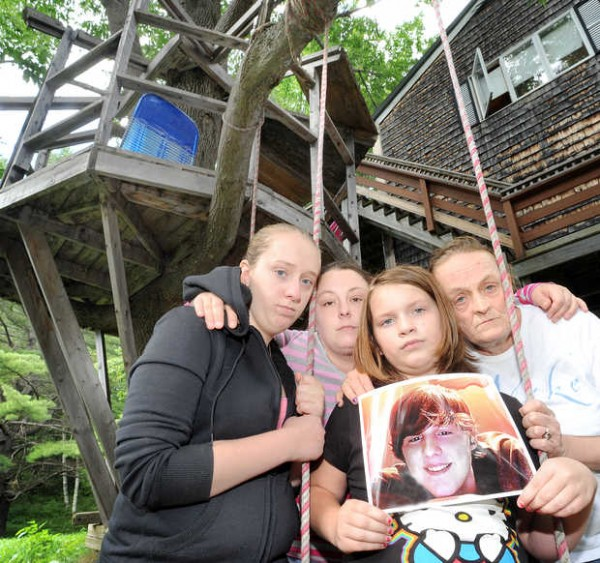 Autumn Thibodeau, 11, sits in the swing she and her brother, Tyla Thibodeau, used to use and holds a photo of him at her grandmother's home in Dixfield on Wednesday. From left are her sister, Ashlie, her aunt Carmen Thibodeau, Autumn Thibodeau, and her grandmother Gerry Thibodeau. In the background is the tree fort Tyla played in.