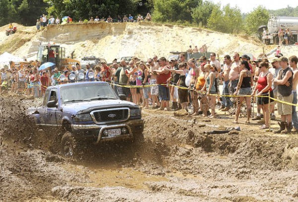 Spectators line the popular mud run as Chuck Spears of Orange, Mass., negotiates the course during last year's Redneck Blank in Hebron on Saturday, Aug. 4, 2012.