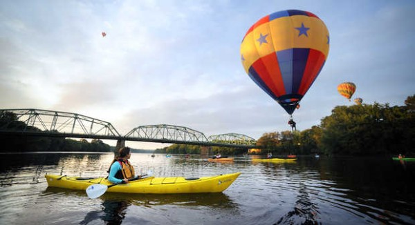 Nichole Bouyea from Lewiston, left, watches as Rick Jones does a splash and dash in his cloud hopper hot air balloon Footloose Sunday morning on the Androscoggin River. Over one dozen kayakers took to the waters on the final morning launch of the 21st Annual Great Falls Balloon Festival.