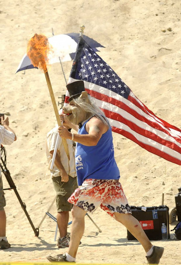 Les Strout, wearing a pig mask, carries the Redneck Blank torch and an American flag in the opening ceremony in Hebron on Saturday. Aug. 4, 2012.