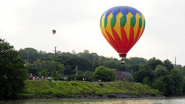 Spectators line the banks of the Androscoggin River in Lewiston to see the final morning launch Sunday.