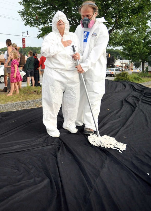 Phyllis Coelho of Belfast pretends to be overcome by fumes as she and Lew McGregor of Hope pretend to clean up an oil spill Wednesday night in Auburn where several dozen people came out to protest the shipments of oil by rail. Three were arrested without incident.