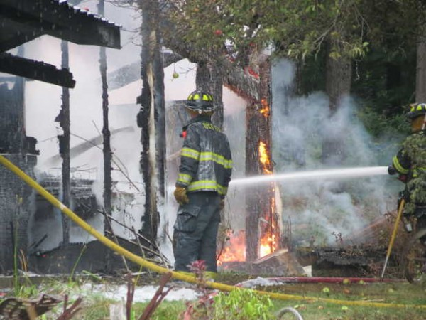 Firefighters douse flames on the back of Laura Freeman's home at 8 Summerland St. in Paris late Thursday afternoon. The fire began in the garage and spread to the house.
