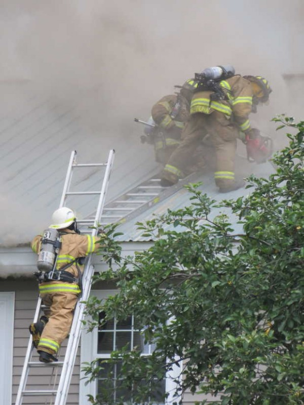 Firefighters cut a hole in the roof of Laura Freeman's burning home at 8 Summerland St. in Paris late Thursday afternoon. The fire began in the attached garage shortly before 5 p.m.