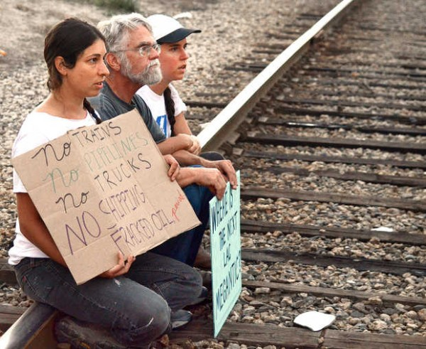 Jessie Dowling, Douglas Bowen Jr. and Meaghan LaSala defy orders from Auburn police to move off the railroad tracks next to Denny's in Auburn on Wednesday evening during a protest against oil being transported over the railways. They were eventually arrested without incident.