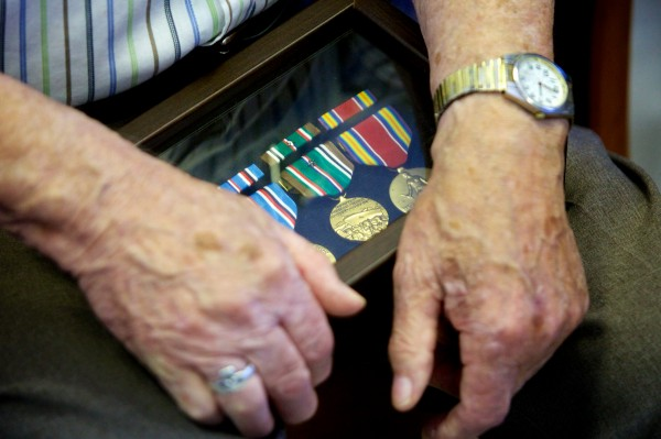 Roger Levesque, 89, holds his new set of military honors, earned in WWII, at a surprise ceremony in U.S. Rep. Chellie Pingree's Portland office Monday. Levesque's original medals were lost in a house fire.