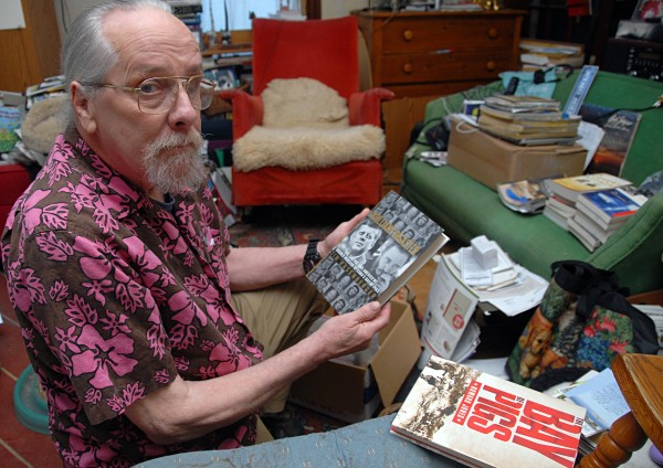 The son of a former deputy director at the CIA, Richard Bissell III of Bangor looks for traces of his late father's work in books visible at his Pearl Street home on Saturday, Aug. 24, 2013.