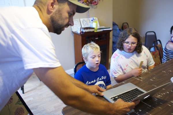Local artist &quotPigeon&quot, left, shows some of his work to Zachary Scott, 9 center, and Solomon Finch, 10, while teaching kids about street art and the art he makes in the Bangor area during a group therapy class Friday afternoon at Higher Ground Services in Brewer.