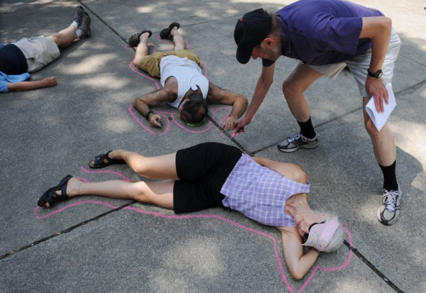 Doug Allen, education coordinator for the Peace & Justice Center in Bangor draws a pink chalk line around people participating in a &quotdie-in&quot during the Peace & Justice's commemoration of the 67th anniversary of the bombing of Hiroshima at Peirce Park in Bangor on Saturday, Aug. 4, 2012.