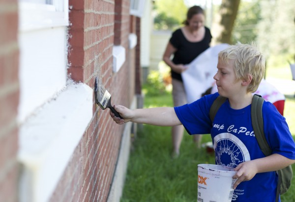 Zachary Scott, 9, puts paste on a wall during a session by local artist &quotPigeon&quot who volunteered to help teach kids about street art and the art he makes in the Bangor area during a group therapy class Friday afternoon at Higher Ground Services in Brewer.