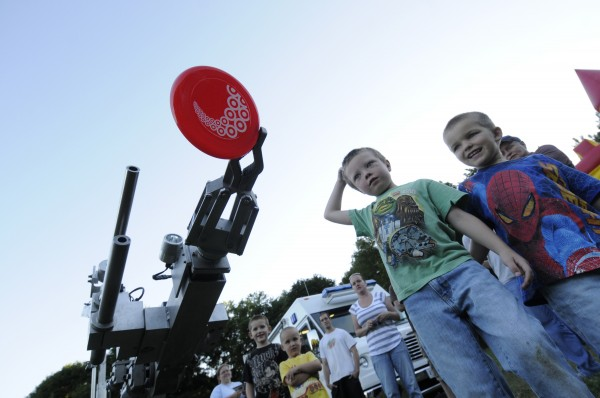 Kolton Kimball (second from right), 5, and Calum Paine (far right), 5, both of Bangor, join other curious onlookers as they enjoy a demonstration of Bangor Police Department's Bomb Squad robot as it picks up Kolton's throwing disc during last year's National Night Out Against Crime event at Second Street Park in Bangor on Aug. 7, 2012.