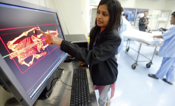 Forensic Medical Officer Dr Kastoori Karuppanan shows the Digital Autopsy forensic application, a three-dimensional capabilities to view and dissect inside and outside of the digital body in high definition visuals at a mortuary at Hospital Kuala Lumpur in Kuala Lumpur July 3, 2013. Malaysian entrepreneur Mathavan Chandran wants to revive the moribund post-mortem by replacing the scalpel with a scanner and the autopsy slab with a touchscreen computer. Infovalley's iGene 3D imaging software is, Chandran says, the first to package the autopsy process and offer it commercially as a suite of services that stretches from the moment of death to the delivery of a post-mortem report.