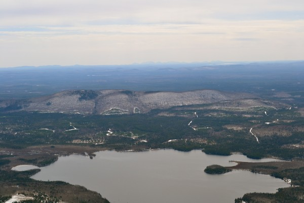 An aerial photo of Passadumkeag Mountain with Saponac Pond in the foreground and the mountains of MDI in the distance.