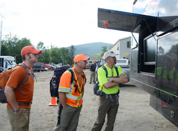Volunteers from Franklin Search and Rescue look over a video display at the Warden Service mobile command post set up at Sugarloaf Mountain on Tuesday, Aug. 5, before heading out to help look for Geraldine Largay, 66, of Brentwood, Tenn. From left are Matt Clark, Marc Keller and Steve Mitman.