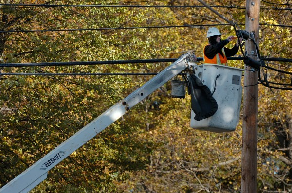 Wes Dempsey of FairPoint Communications finishes work on a cable line in an east side Bangor neighborhood in October 2009.