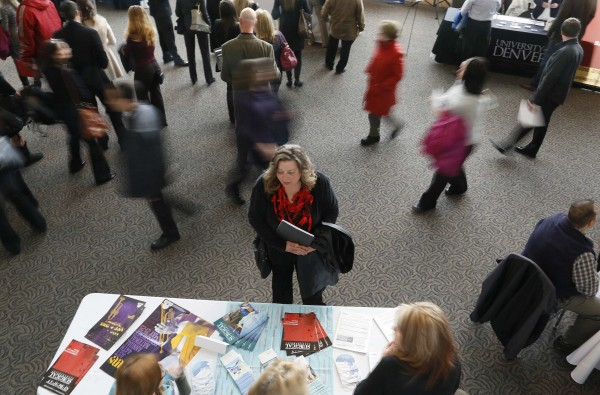 File photo of a job seeker talking to an exhibitor at the Colorado Hospital Association health care career fair in Denver.
