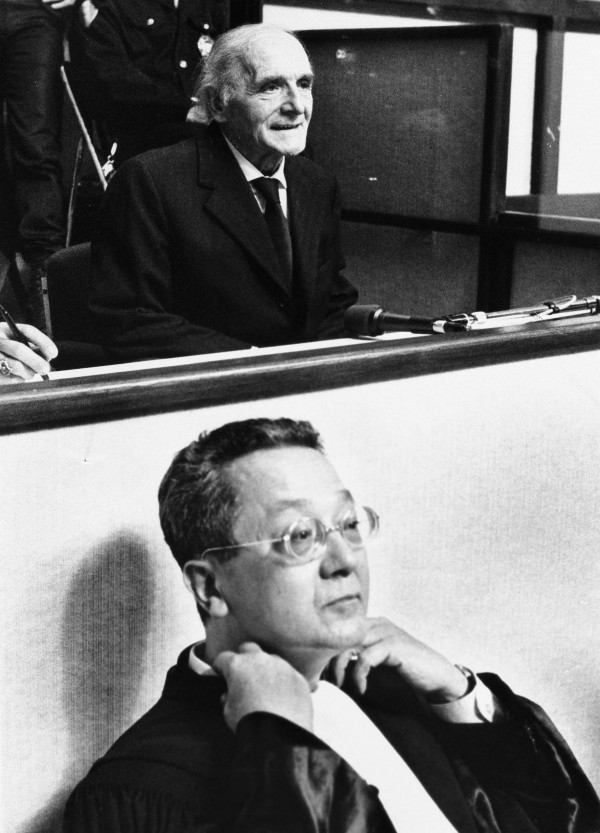 French lawyer Jacques Verges (foreground) sits in front of former Gestapo officer Klaus Barbie who sits behind a glass screen before the Lyon Assize court at the opening of his trial May 11, 1987.
