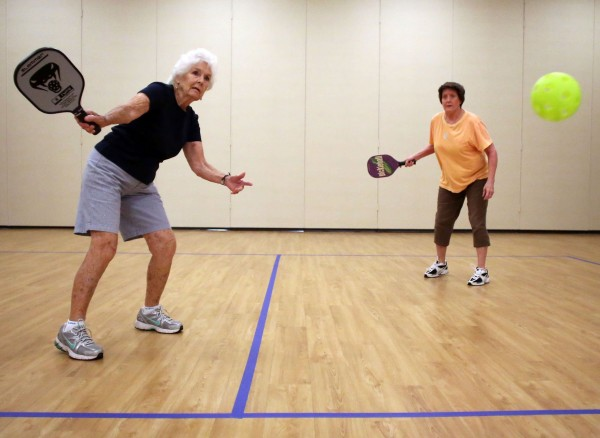 Jay Massey (left) returns a volley as her teammate Betty Bailey watches as they play pickleball at the Five Points Center for Active Adults in Raleigh, N.C., recently.