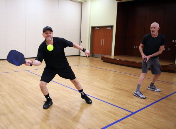 Francis Ganchegui (left) and teammate Jim Durnim play pickleball at Five Points Center for Active Adults in Raleigh, N.C., recently.