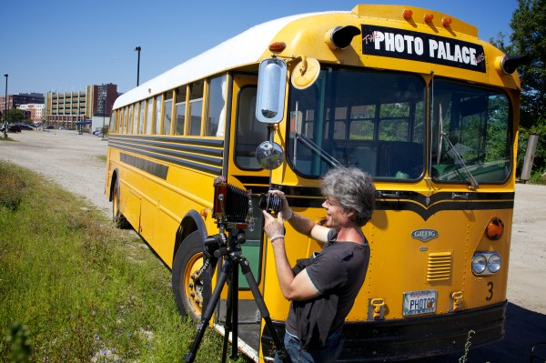 Anton Orlov gets his 4x5 view camera ready to make photographs Saturday in Portland. Orlov is traveling the country in the Photo Palace Bus, a mobile darkroom, built into an old school bus, dedicated to analog photography.