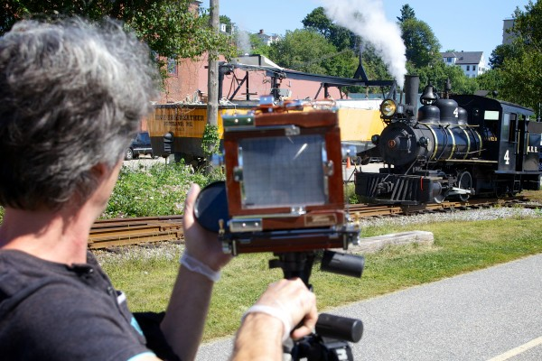 Anton Orlov  makes picture of a steam train Saturday in Portland. Orlov is traveling the country in the Photo Palace Bus, a mobile darkroom, built into an old school bus, dedicated to analog photography.
