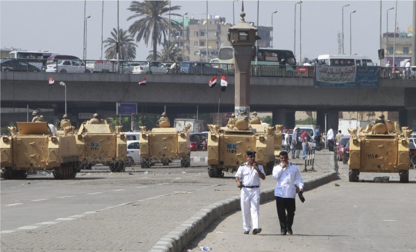 Egyptian army soldiers guard with armored personnel carriers near Tahrir Square in Cairo August 19, 2013. Suspected Islamist militants killed at least 24 Egyptian policemen on Monday in the Sinai peninsula, where attacks on security forces have multiplied since the army overthrew President Mohamed Mursi on July 3.