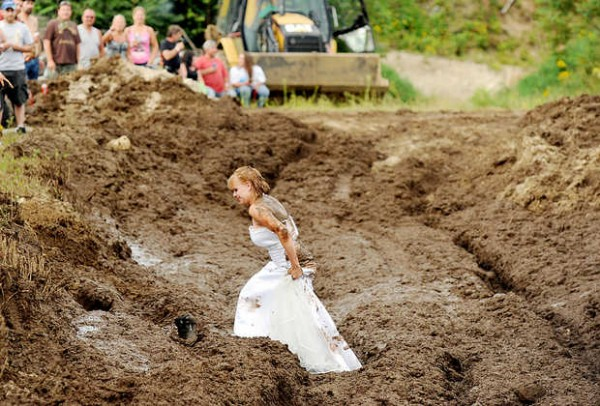 Lucretia (Blais) Gould walks through the mud run pit in her wedding dress after getting married to Jeff Gould at the Redneck &quotBlank&quot in Hebron on Saturday.