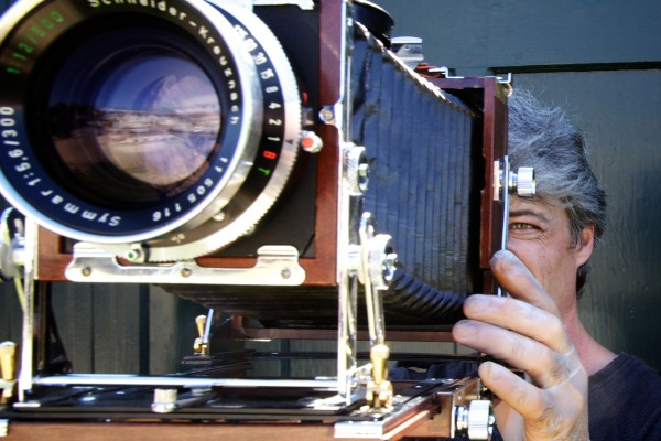 Anton Orlov aims his 4x5 view camera while making photographs Saturday in Portland. Orlov is traveling the country in the Photo Palace Bus, a mobile darkroom, built into an old school bus, dedicated to analog photography.