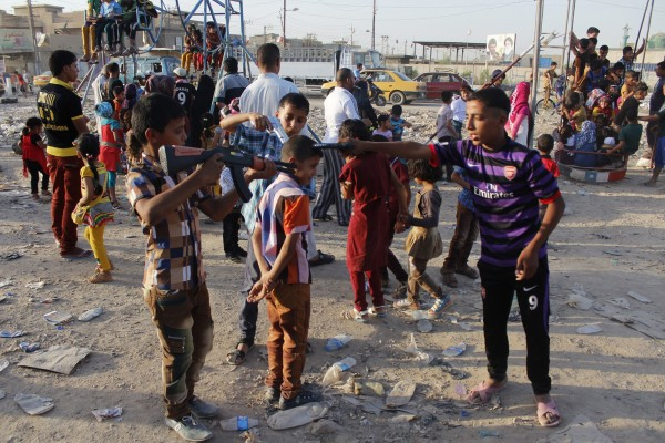 Children play with toy guns at an amusement park as they celebrate Eid al-Fitr in Baghdad on Saturday. The day of celebration was marred by 10 car bombing, which killed 50 people.