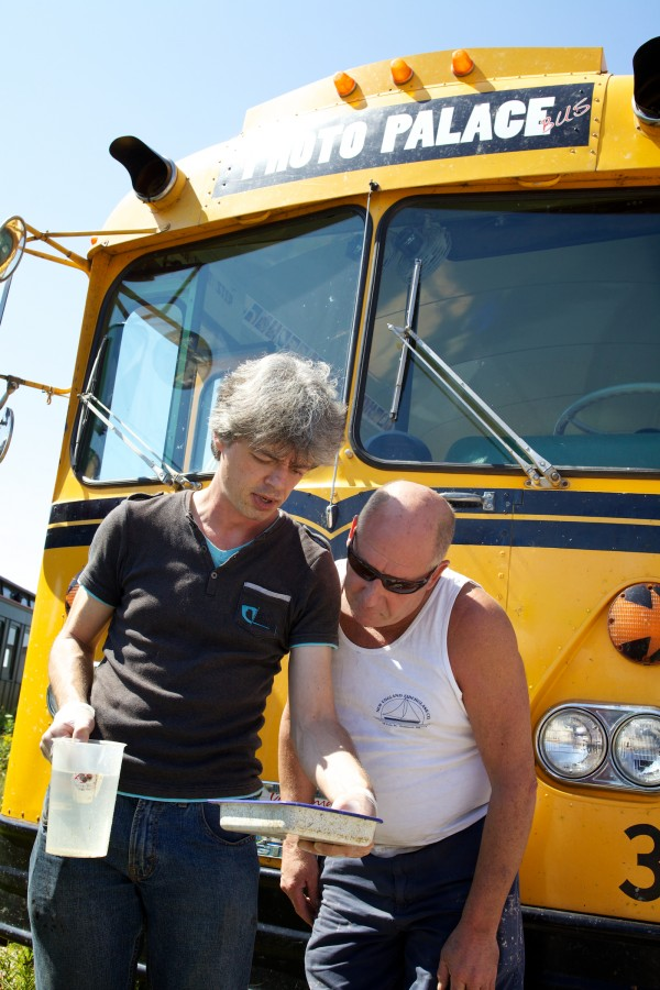 Anton Orlov shows Dave Hoar, who works nearby, an ambrotype photograph Saturday in Portland. Orlov is traveling the country in the Photo Palace Bus, a mobile darkroom, built into an old school bus, dedicated to analog photography.