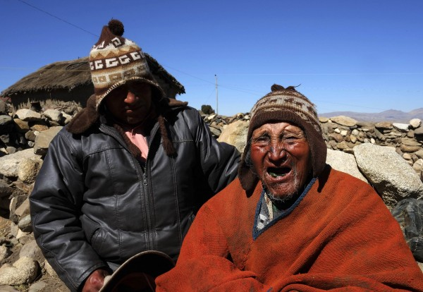 Aymara Indian Carmelo Flores (R) and his son Cecilio joke during a Reuters TV interview in his hometown of Frasquia, 110km (68 miles) north of La Paz, August 16, 2013. According to Flores' identification card, he was born in 1890 and celebrated his 123rd birthday last month, making him the world's oldest man. Flores, who used to work as a farmer, has lived next to Bolivia's highest mountain, the Illampu, for his entire life. He eats what can hunt, like snake, lizard and fox, only drinks mountain spring water, chews coca leaves, avoids sugar and says that he has never been seriously ill.