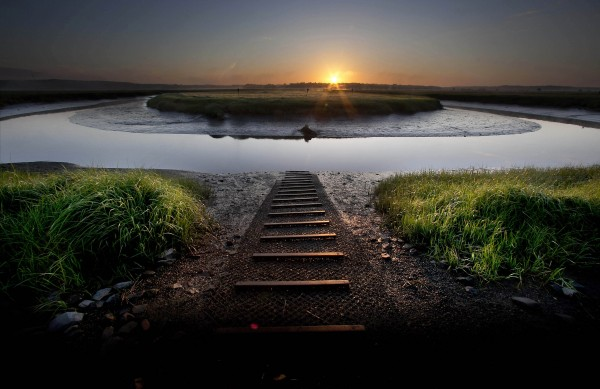 The sun rises over an oxbow curve at the Scarborough Marsh in Scarborough, Maine, Sunday, June 17, 2012. A boat ramp leads to the water over the muddy bank in the foreground.