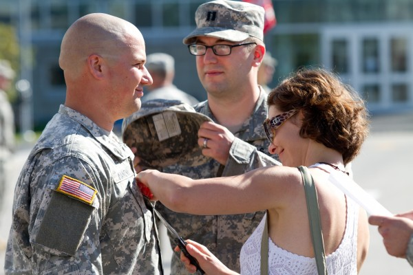 Carrie Mancini uses a knife to remove her husband's old rank insignia during a promotion ceremony on the University of Southern Maine campus Saturday morning. Captain Mark Mancini is deploying with the 133rd Engineer Battalion next week.
