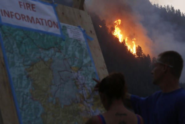 People look at a map of the fire as flames leap at the Beaver Creek wildfire outside Hailey, Idaho August 18, 2013. Firefighters readied for a massive ground and air attack on Sunday against a wildfire in central Idaho that has forced the evacuation of some 2,250 homes and threatens the posh Sun Valley ski resort.