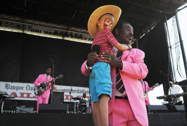 Dennis Bowers, lead singer with The Legendary Singing Stars, hugs Owen Beane of Orono as he performs a gospel song on Sunday during the American Folk Festival on the Bangor Waterfront.
