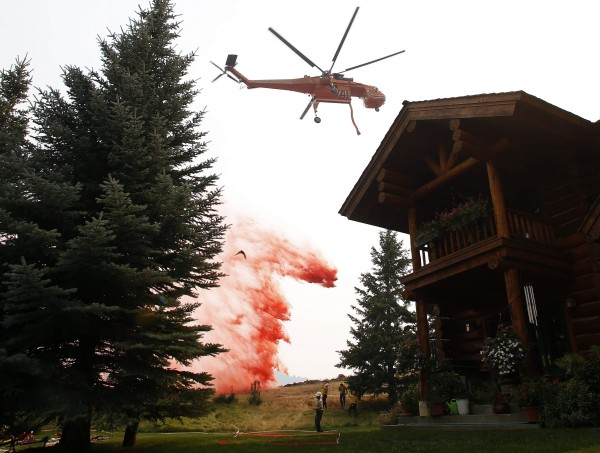 A helicopter tanker drops fire retardant near a home at the Beaver Creek wildfire outside Ketchum, Idaho August 18, 2013. Firefighters readied for a massive ground and air attack on Sunday against a wildfire in central Idaho that has forced the evacuation of some 2,250 homes and threatens the posh Sun Valley ski resort.