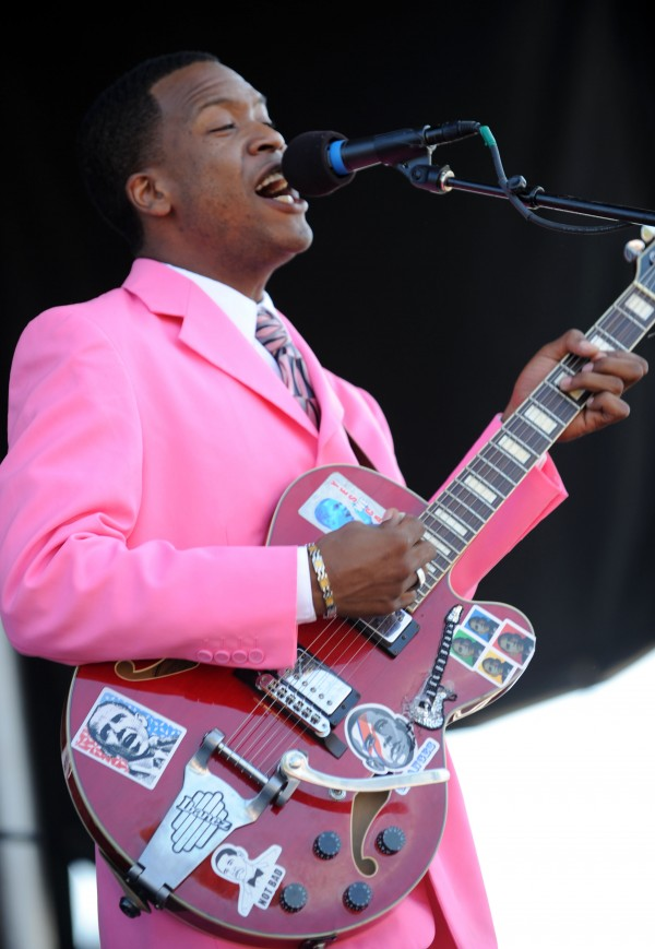 Da'Quan  Bowers, lead guitarist with The Legendary Singing Stars, performs with Obama stickers on his guitar during a gospel set on Sunday during the American Folk Festival on the Bangor Waterfront.