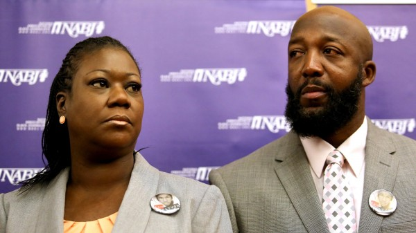The parents of Trayvon Martin, Sybrina Fulton, left, and Tracy Martin, listen to their attorneys, during a news conference at the National Association of Black Journalists national convention, in Orlando, Florida, Friday, August 2, 2013.