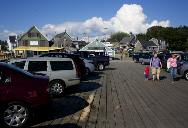 Visitors walk along a pier in front of the Monhegan Boat Line dock Wednesday afternoon in Port Clyde, Maine just days after the August 11 crash that killed a child, injured a family and damaged several parked cars.